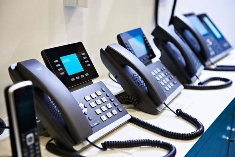 Office phones lined up on a desk