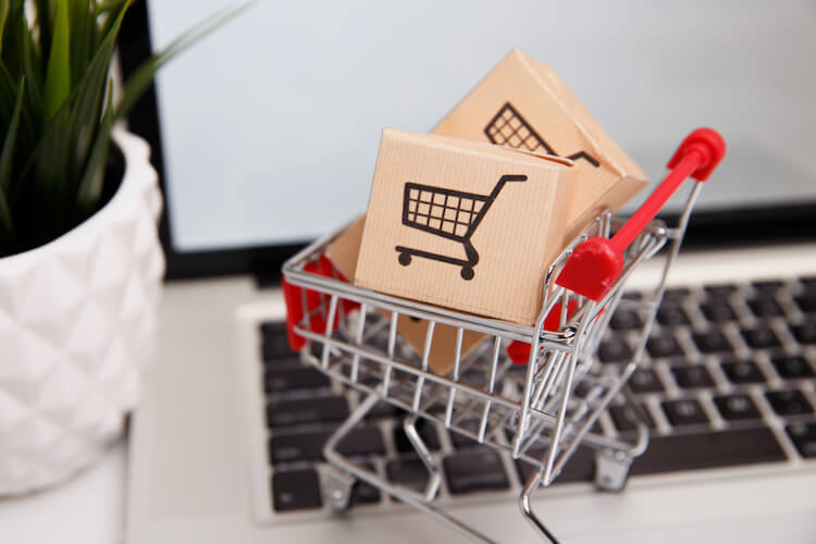 Mini shopping trolley full of boxes on laptop keyboard