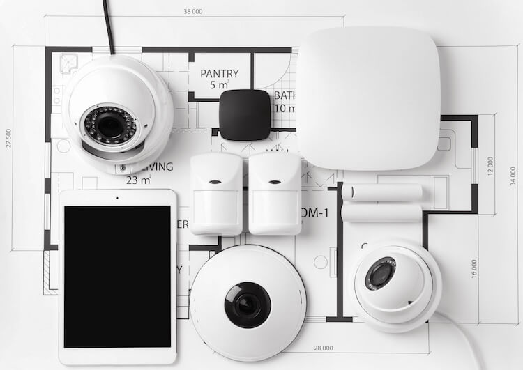 An array of cameras, tablets, and security devices laid out on a set of schematic plans