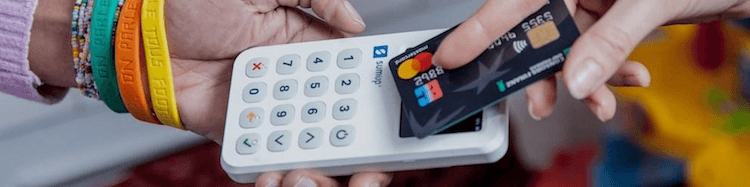 Woman taking payment with a SumUp card reader