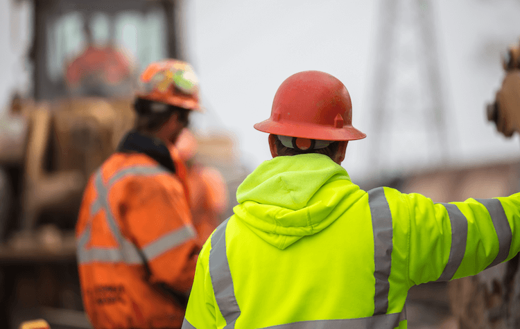 Construction worker surveying a site