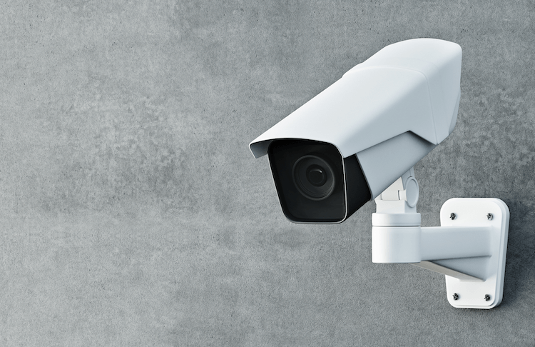 White security camera mounted on grey wall featured image