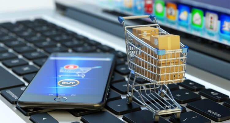 Smartphone sitting on keyboard next to trolley full of packages