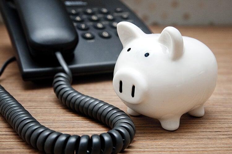 Piggy bank next to an office telephone
