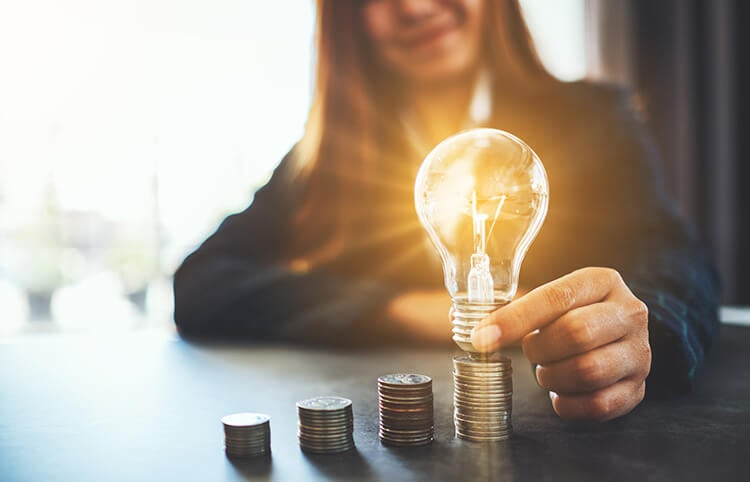 Woman placing lightbulb on top of coins