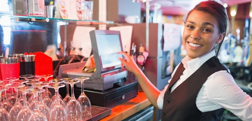 Female server at a bar using an EPOS system